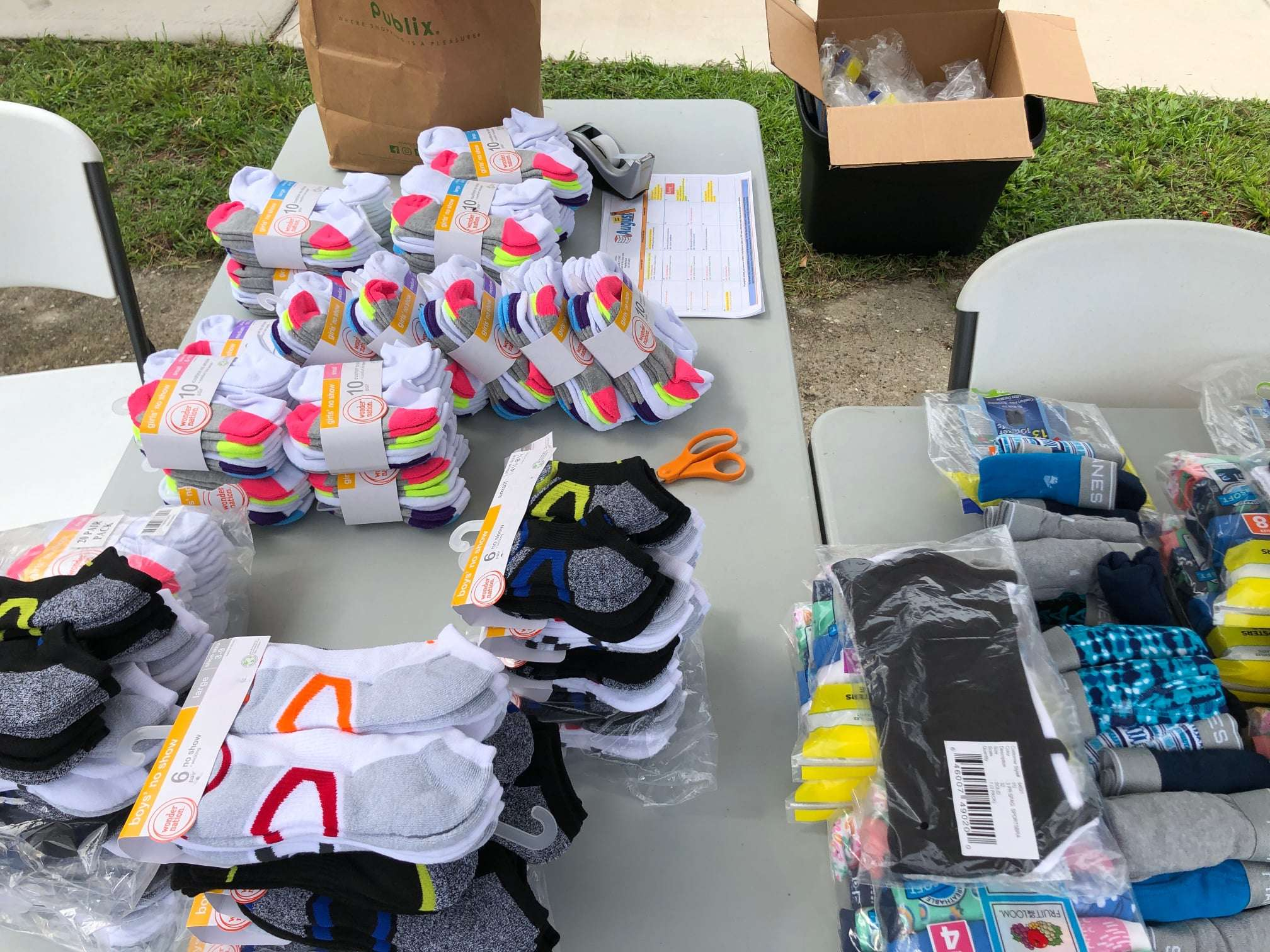 Packages of new kids' socks and underwear are laid out on a table to be given to families along with back-to-school supplies
