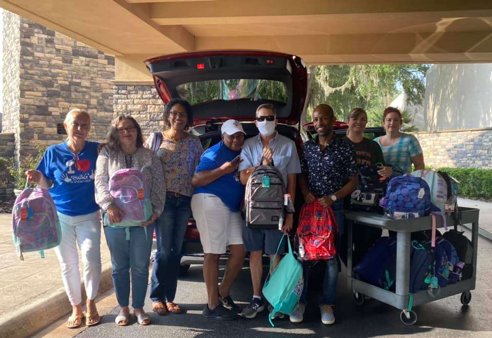 SWAG board members, Resource Center staff, and Tower Hill Insurance staff stand together with newly donated backpacks