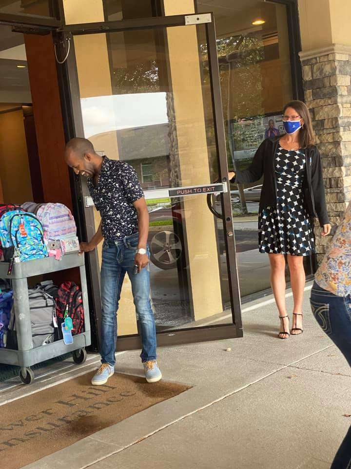 A Tower Hill Insurance staff member holds the door while a second pulls a cart full of back-to-school backpacks.