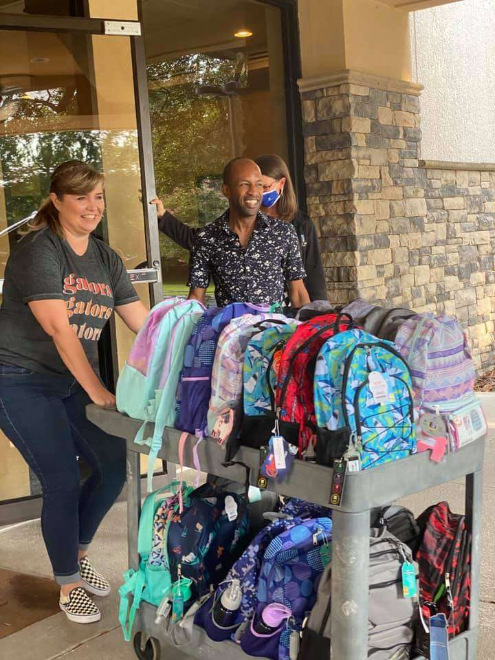 A Tower Hill Insurance staff member pushes a cart full of back-to-school backpacks to be donated to SWAG.