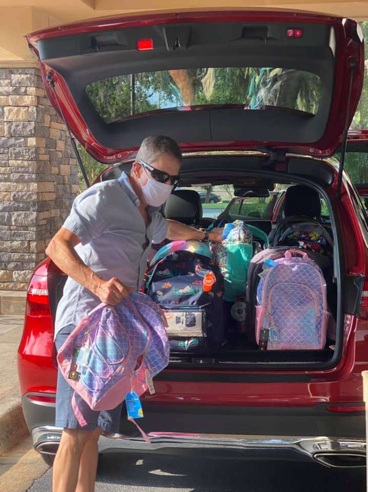 A Tower Hill Insurance staff member loads a car full of backpacks for SWAG families
