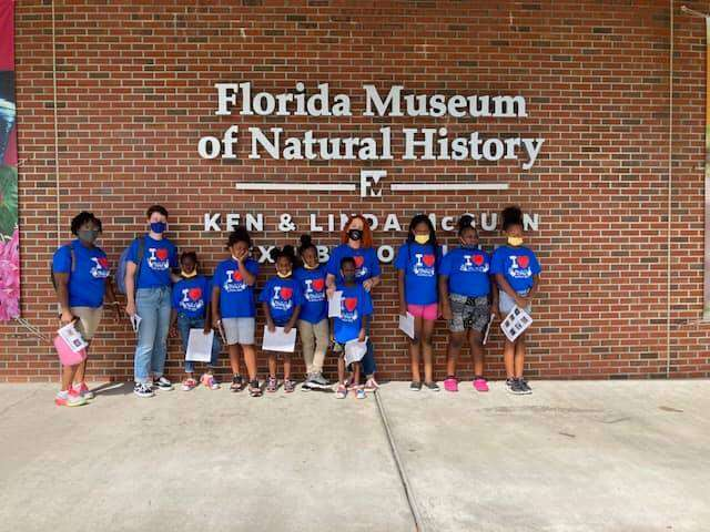 SWAG summer session students stand together in front of the sign naming the Florida Museum of Natural History