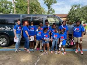 Kids attending SWAG's summer session stand together in front of a Partnership for Strong Families van for a field trip