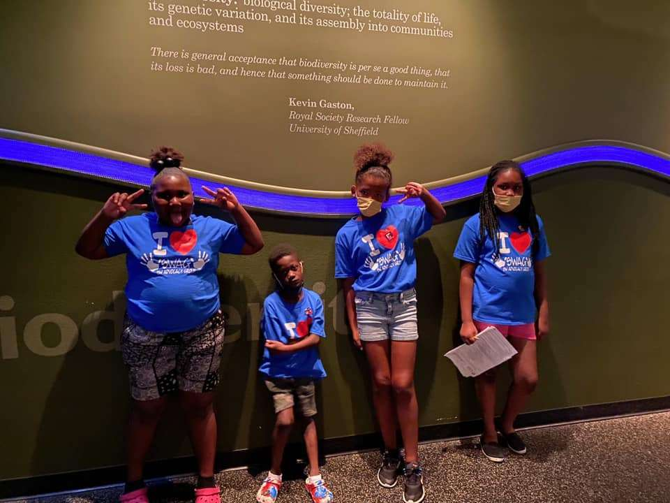 Four SWAG summer session students pose together next to a museum exhibit during a July 2021 field trip