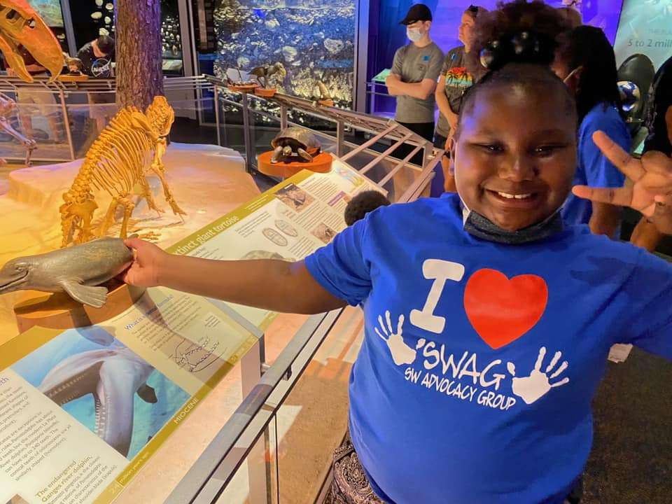 """A child wearing a SWAG shirt makes a """"peace"""" sign and smiles while interacting with a Florida Natural History Museum exhibit"""