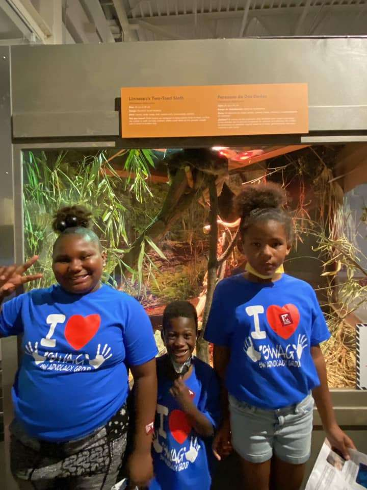Three SWAG summer session students pose together next to a museum exhibit during a July 2021 field trip
