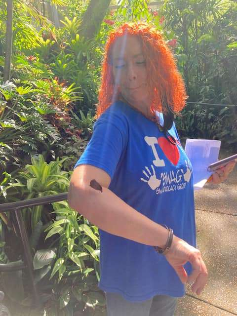 The SWAG Family Resource Center's Robin Wilkerson wearing a SWAG tee shirt and looking at a butterfly perched on her arm