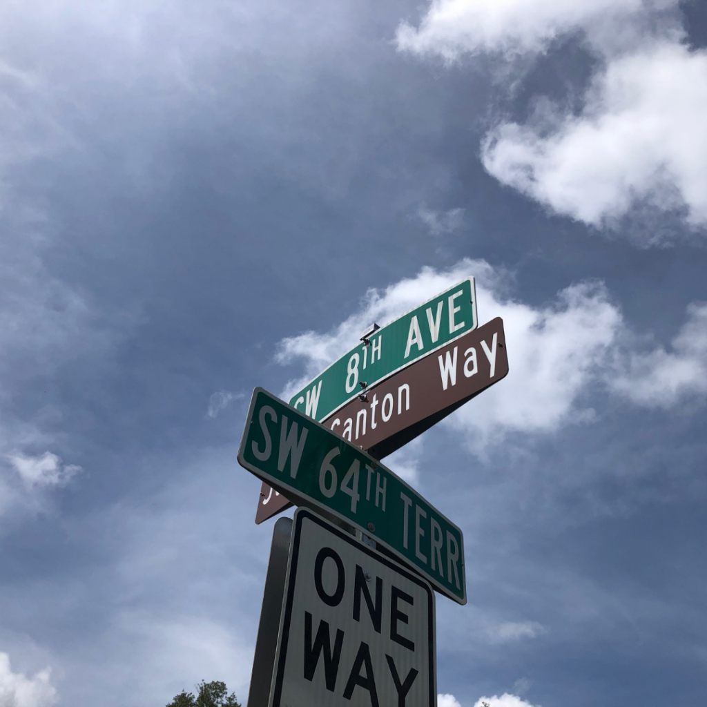 The new brown street sign for Joan Canton Way between signs for SW 8th Avenue and SW 64th Terrace