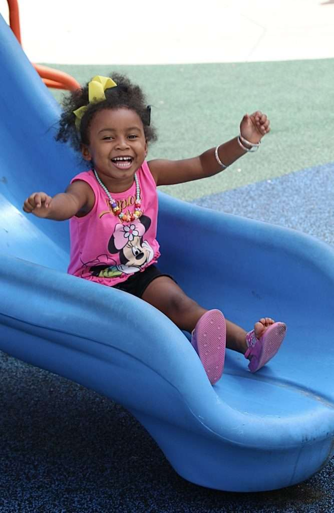 A young child smiles widely as she reaches the bottom of a blue slide on the playground by the SWAG Family Resource Center