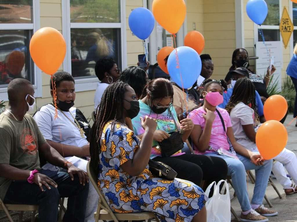 Friends and family of Joan Canton sit in front of the SWAG Family Resource Center for a road naming ceremony in Joan's honor