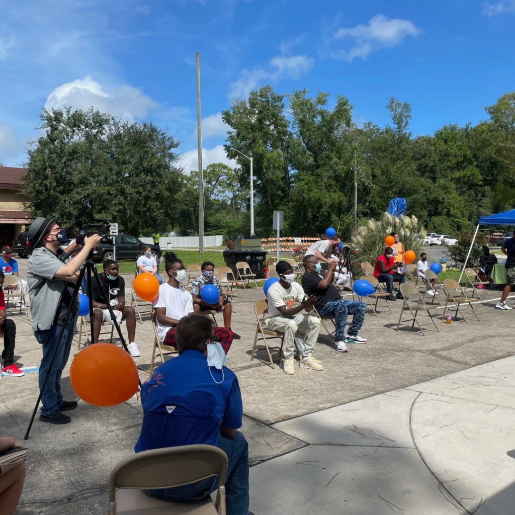 An audience and County videographer watch the road naming ceremony for Joan Canton Way