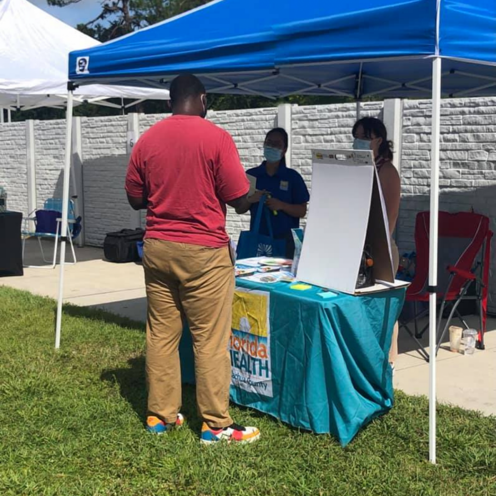 A community member visits the Alachua County Department of Health booth at the Community Connections resource fair