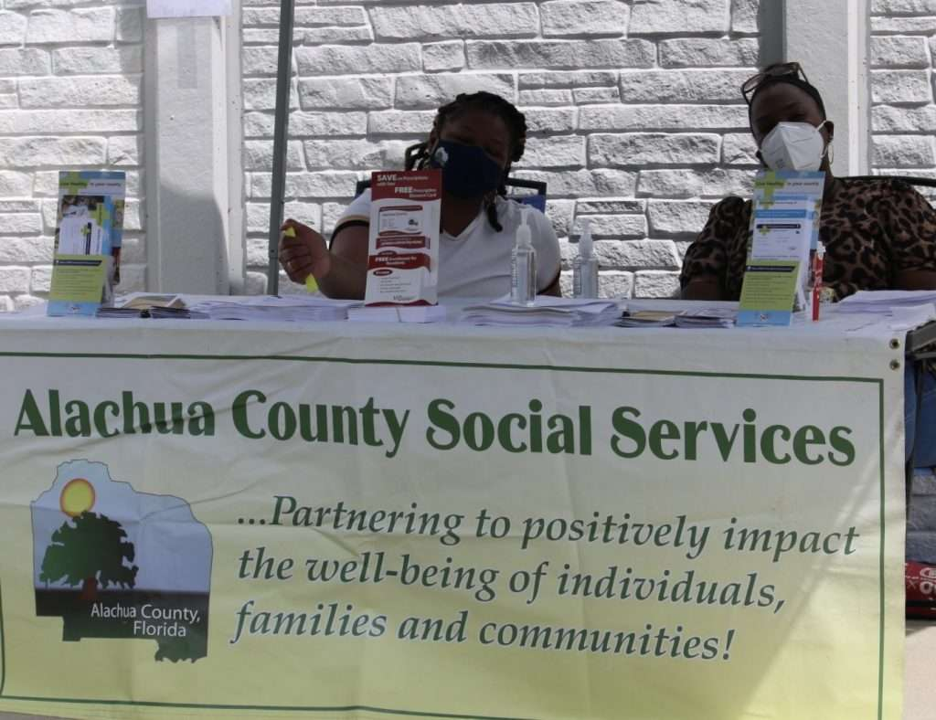Two Alachua County employees staff a booth for the County's Department of Social Services at the Community Connections Celebration
