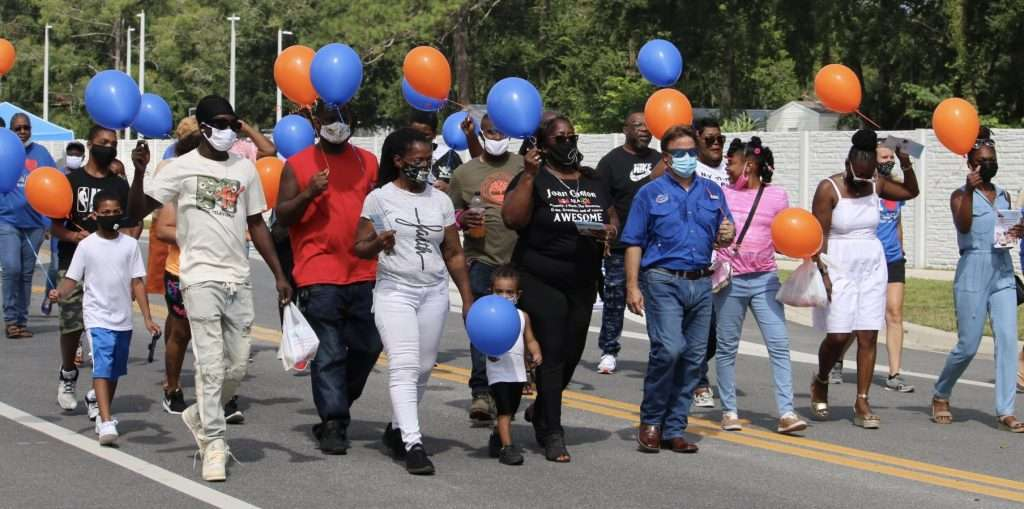 Friends, family, and community members walking along the newly named Joan Canton Way with orange and blue balloons