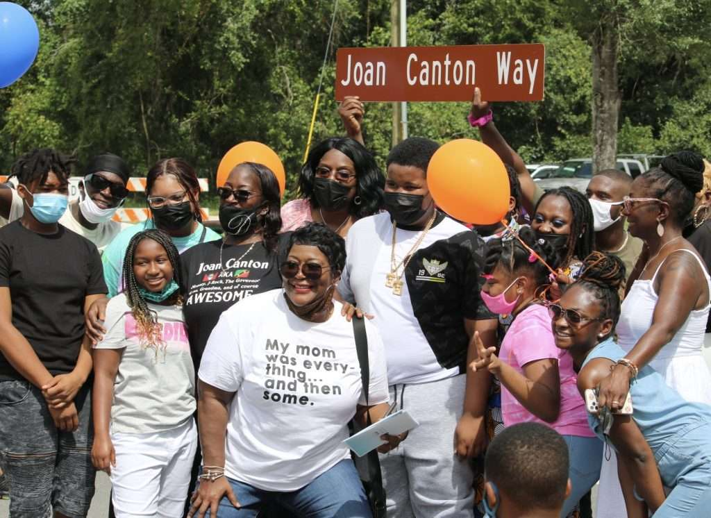 """Family and friends of Joan Canton pose with big smiles, holding a street sign that reads, """"Joan Canton Way."""""""