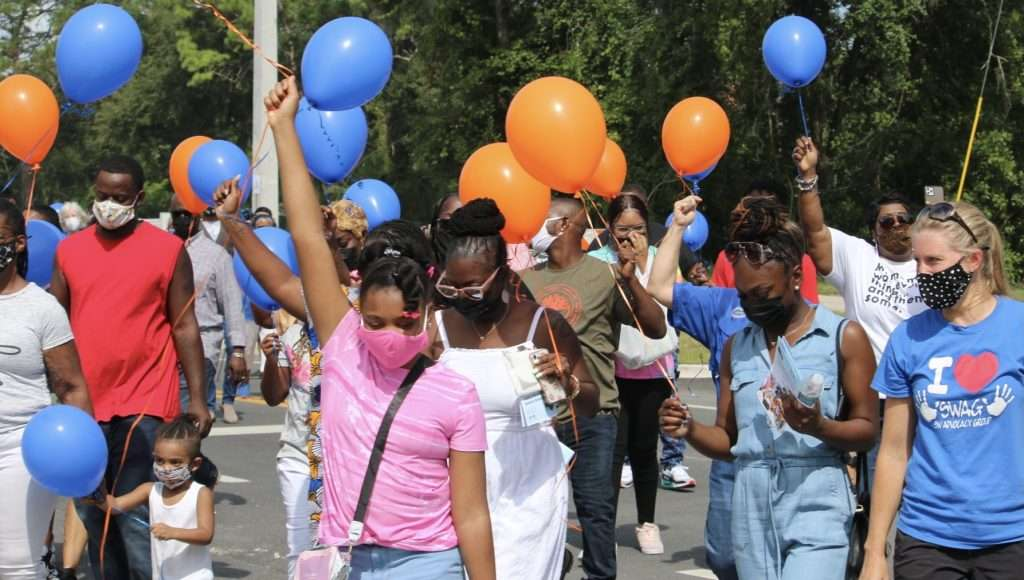 Family and friends of Joan Canton hold up orange and blue balloons as they walk along the newly-named Joan Canton Way.