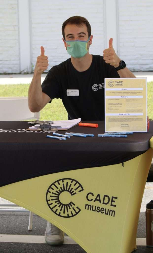 A Cade Museum staff member gives two thumbs-up at the Cade booth during the Community Connections Resource Fair