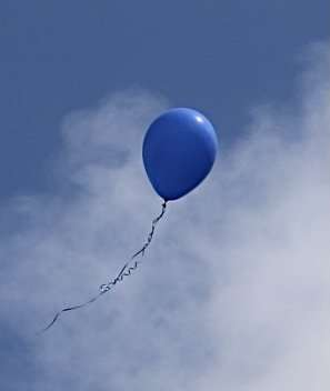 A blue balloon floats upward into a blue sky with white, wispy clouds during the road naming ceremony for Joan Canton Way