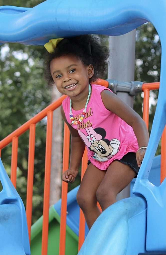 A young child prepares herself to go down the slide on the playground next to the SWAG Family Resource Center