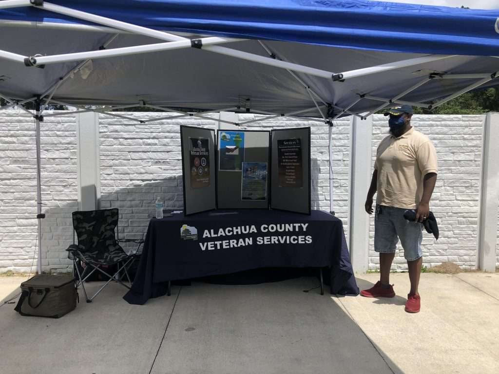 A County employee staffs an Alachua County Veteran Services booth at the SWAG Community Connections resource fair