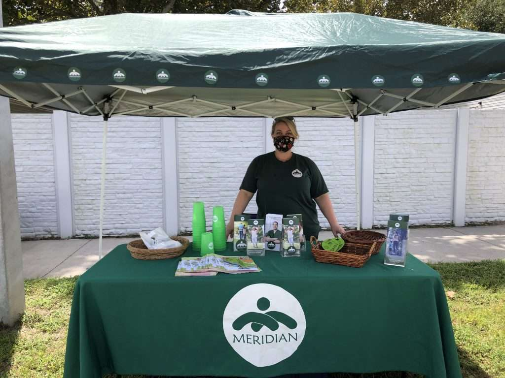A Meridian Behavioral Healthcare employee staffs a resource booth during the Community Connections Celebration