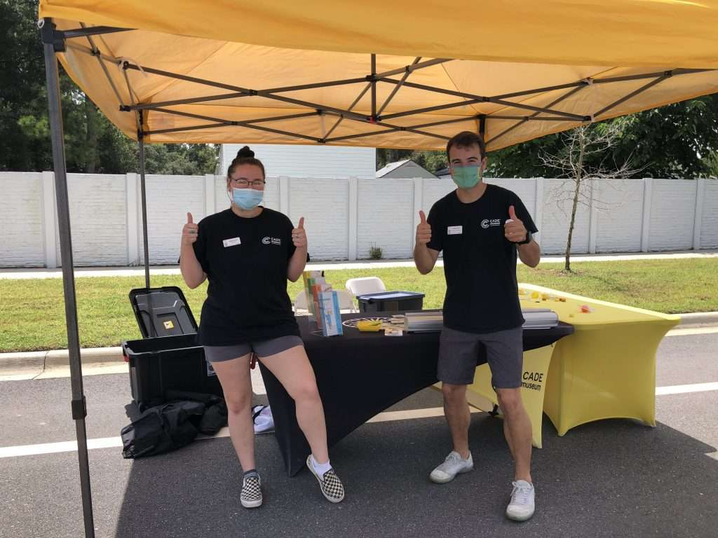 Two Cade Museum staff give two thumbs-up at their booth during the Community Connections resource fair.