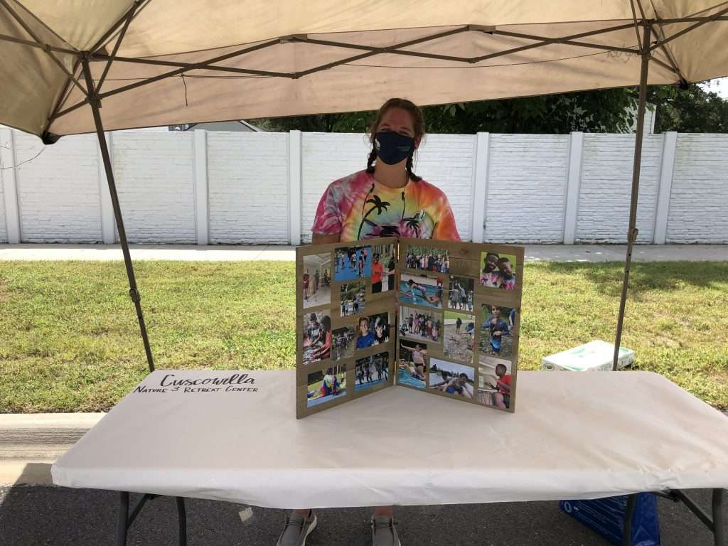 A County staff member stands behind a photo display in a Cuscowilla booth for during the Community Connections Celebration