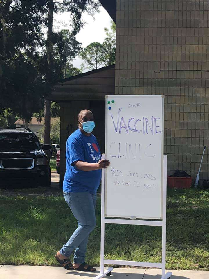 A SWAG volunteer wheels a sign advertising the free COVID-vaccine mobile clinic