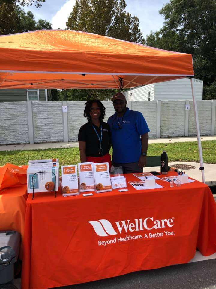 Two WellCare Health Plans staff stand in front of their resource booth during the Community Connections Celebration